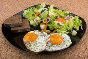uova fritte con insalata e pane freschi