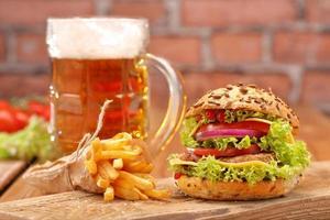 hamburger alla griglia con patatine fritte e birra su sfondo di muro di mattoni foto