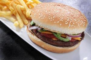 hamburger in panino seminato con patatine fritte e insalata