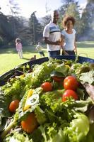 famiglia con barbecue all'aperto, piatto di insalata in primo piano foto