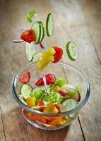 verdure fresche che cadono nella ciotola di vetro