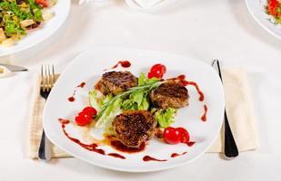tagli di carne alla griglia con verdure sul piatto bianco