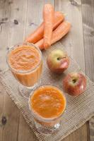 frullato di carota mela in un bicchiere foto