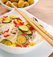 tagliatelle di riso e verdure sul piatto bianco