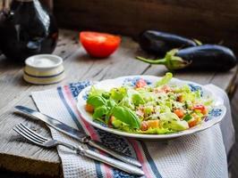 insalata di verdure verde con pomodoro, semi di sesamo e lino, basilico