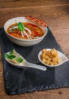 zuppa di verdure servita con pancetta croccante, formaggio e crocchette foto