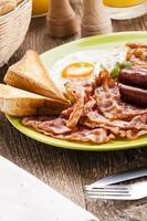 colazione inglese completa con pancetta, salsiccia, uovo fritto, bea al forno