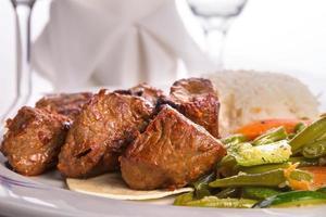 scatti macro di shish kebab e verdure cotte foto