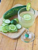i vetri con acqua fresca organica del cetriolo sulla tavola di legno foto
