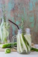 barattoli di vetro di cetriolo e rosmarino sul tavolo di legno foto