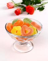 caramelle colorate con cuori rossi in ciotola di vetro e rose
