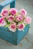 rose in un vecchio cestino da giardinaggio in legno blu foto