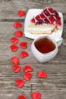 tazza di tè, fetta di torta e cuore rosso foto