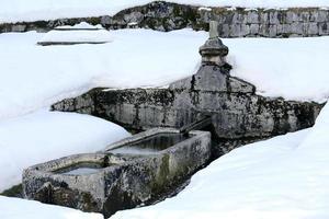 grande fontana in pietra con acqua fredda gelida in montagna foto
