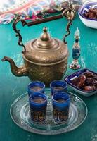 tè mediorientale e palma da datteri sopra fondo di legno foto