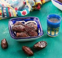 palma da dattero e tè mediorientale su sfondo di legno foto