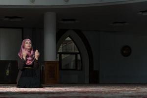 donna musulmana che prega nella moschea foto