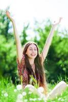donna con le braccia alzate in prato foto