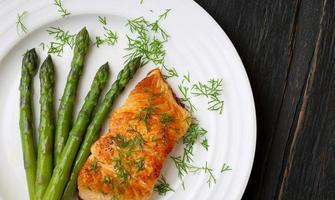 filetto di salmone con asparagi sul piatto bianco