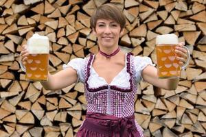 donna bavarese felice che tiene due boccali di birra foto
