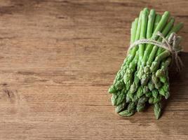mazzo di asparagi sul tavolo di legno foto