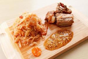 costine di maiale arrosto pronte con pomodoro, carote e cavolo foto