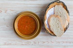 ciotola di zuppa di minestrone con pane sul tavolo di legno foto