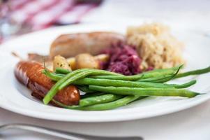 Salsiccia svizzera e fagiolini sul piatto bianco