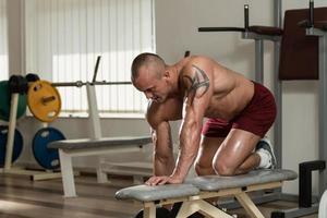uomo in buona salute che fa gli esercizi di schiena con la testa di legno