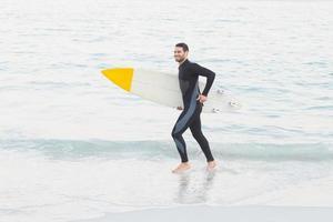 uomo in muta con una tavola da surf foto