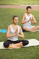 esercizio di yoga. giovane coppia meditando nel parco estivo foto