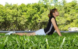 le giovani donne esercitano yoga con orizzontale sul pascolo foto