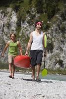 germania, baviera, uomini terrestri tölzer che trasportano sorridenti remi kayak foto