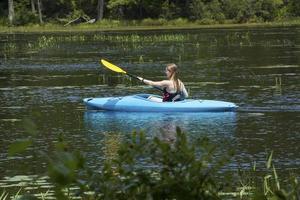 giovane donna in kayak, acqua in sunapee, New Hampshire, Horizonta foto