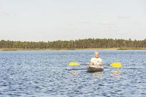 l'uomo sta guidando il kayak in acqua foto