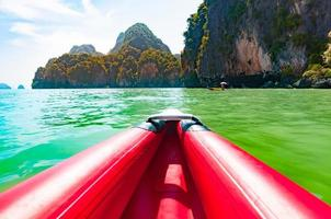 canoa nella baia di phang nga lungo le grandi rocce calcaree foto