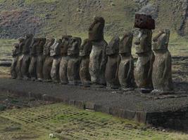 fila di moai contro la montagna foto