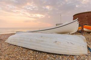 barche a remi su una spiaggia, contro un tramonto foto