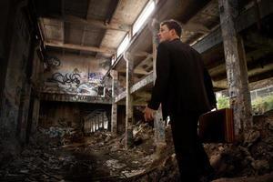 uomo d'affari confuso all'interno di un edificio distrutto