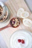 muesli sul cucchiaio con una ciotola di yogurt foto