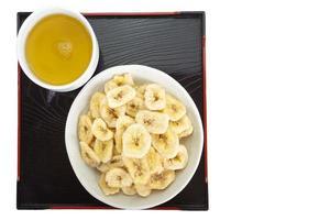 croccanti patatine di banana mangiano con tè caldo foto