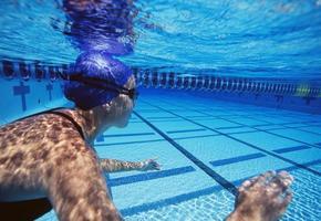 nuotatori femminili caucasici che nuotano nello stagno foto