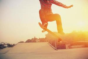 uno skateboarder che salta la sua tavola in uno skate park al tramonto foto