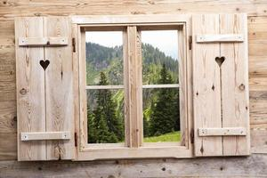 finestra in legno con riflessi montani foto