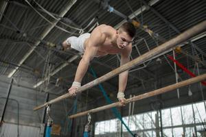 atleta in topless facendo esercizi sulle barre irregolari