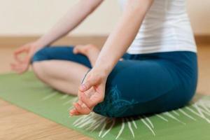 donna caucasica sta praticando yoga in studio (ardkhapadmasana) foto