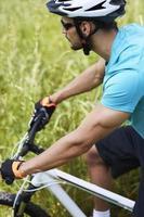 uomo in bicicletta attraverso il prato foto