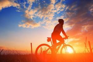 sagoma di un motociclista e bicicletta su sfondo tramonto. foto