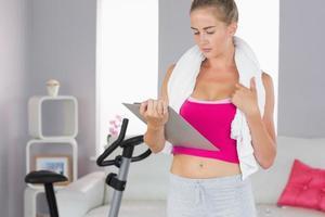 Appunti studiando bionda seria sportiva e tenendo asciugamano foto