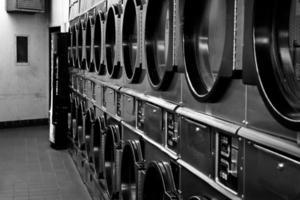 lavatrici e asciugatrici in lavanderia a gettoni in bianco e nero foto